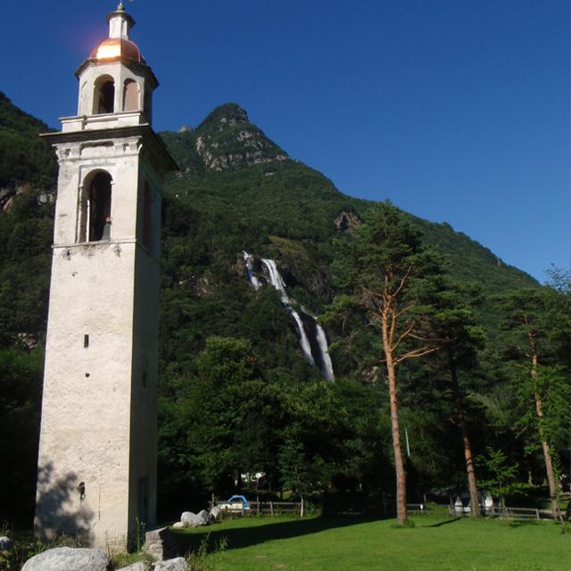 kerktoren met grasveld waterval en berg op achtergrond