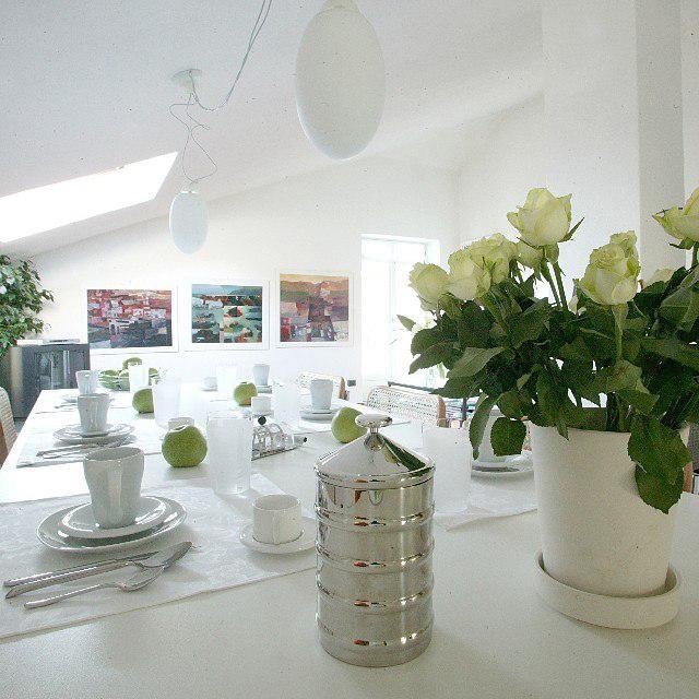 strakke witte tafel gedekt voor ontbijt met witte vaas met groen rozen