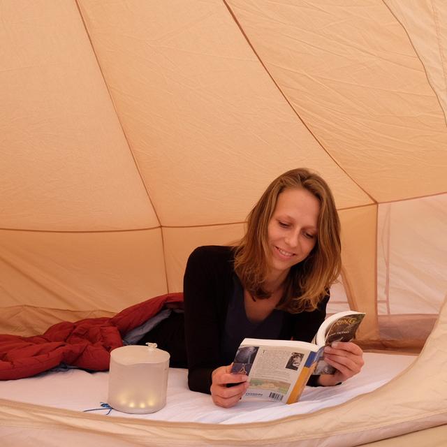 Vrouw ligt op matras in tent en leest boek