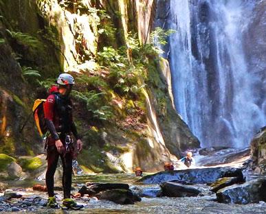 canyongids kijkt achterom naar waterval