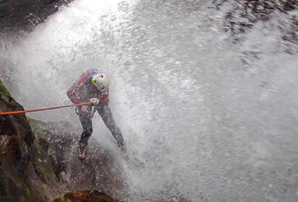 man abseilt door grote witte waterstraal ijdens canyoning