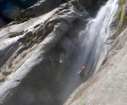 canyoneer abseilt door waterval met 'thumbs up'