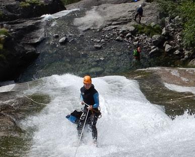 vrouw in canyoningpak abseilt door waterval van bovenaf gezien