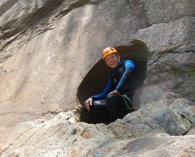 jongen in wetsuit zit in een rond gaat in de rotswand tijdens canyoning