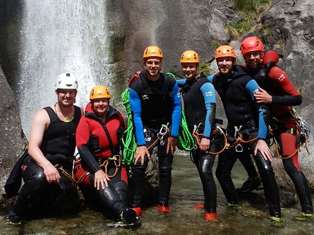 groepsfoto van mensen voor een waterval met canyonuitrusting