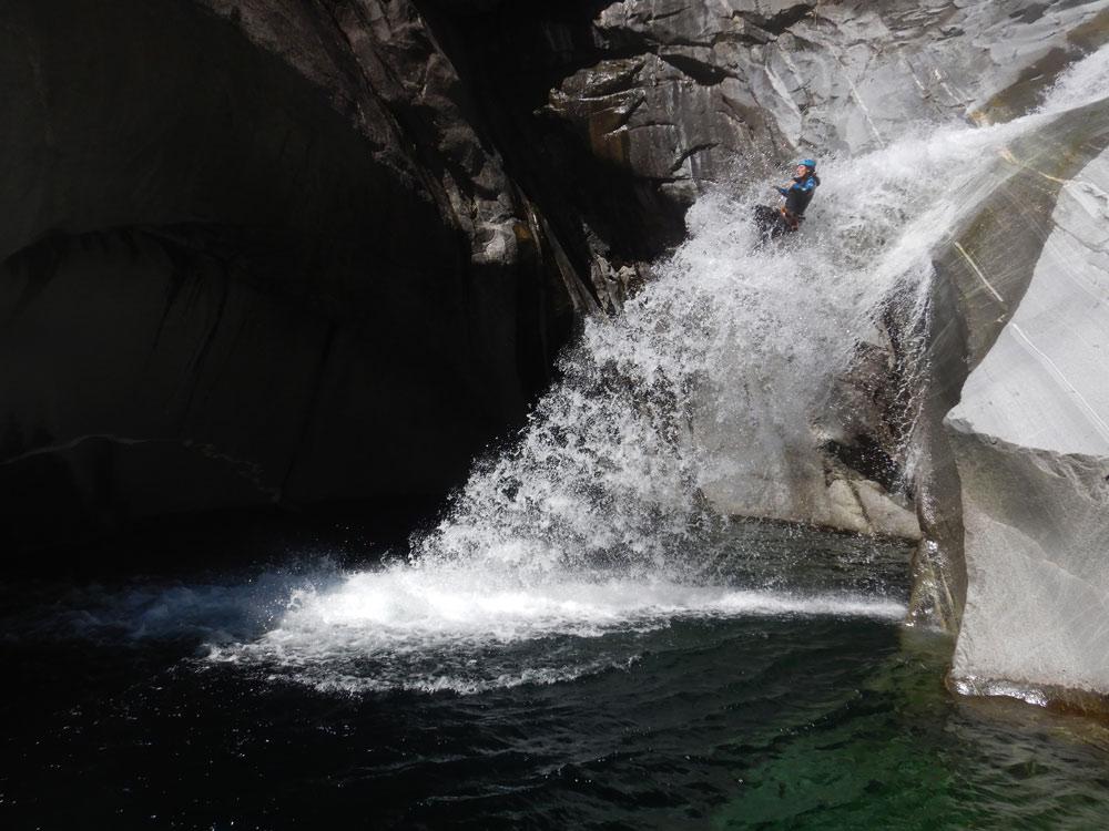 canyoneer glijdt van watervalglijbaan