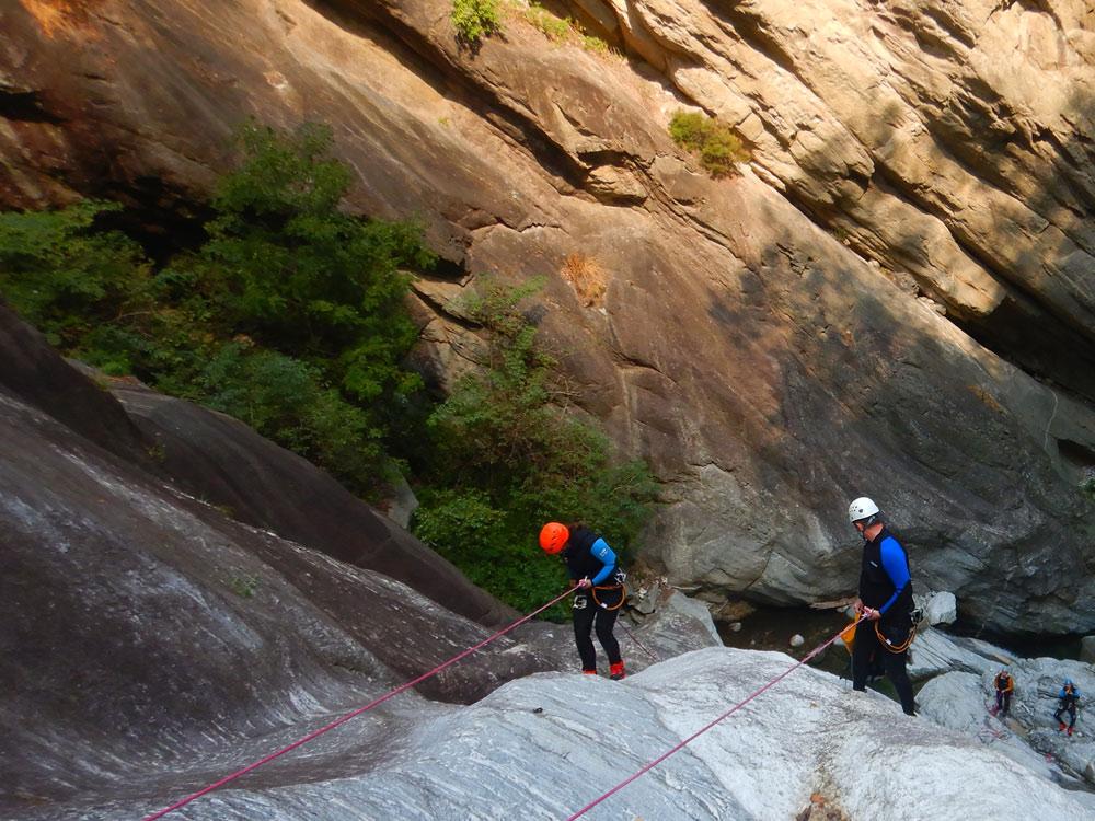 twee mensen die abseilen in een bergkloof en onderaan twee mensen die op hen wachten en naar boven kijken.
